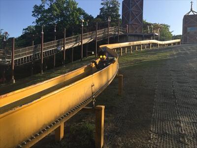 くりはま花の国の冒険ランドのローラーすべり台で滑る子供